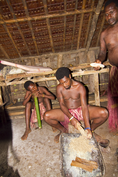 Villager shreds kava from a root like the one Chief Bule Kone, right, holds. Photo by David Lansing.